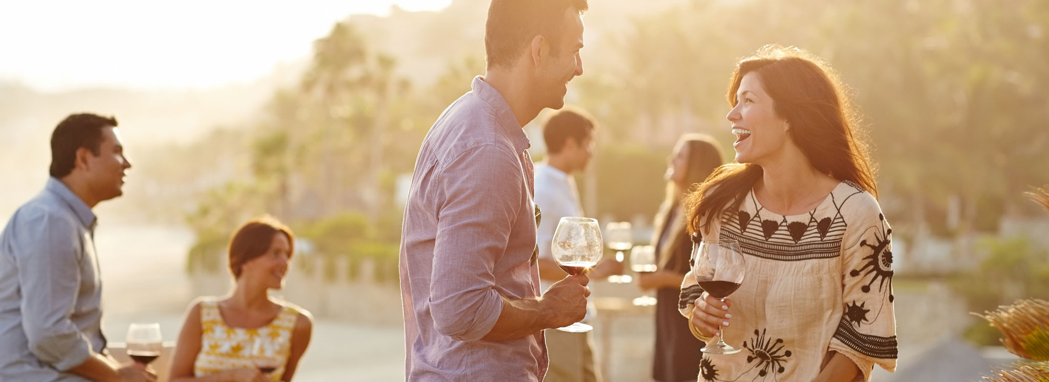 Man and woman laughing while holding glasses of wine